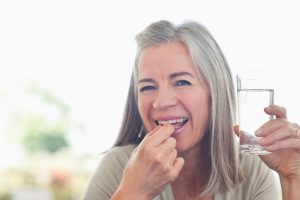 Happy mature woman takes a vitamin supplement.