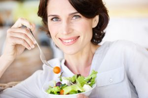 Image of woman enjoying a nice, fresh salad.