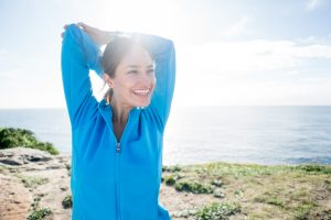 Woman smiling with arms stretched as she enjoys her walk and the fresh air.