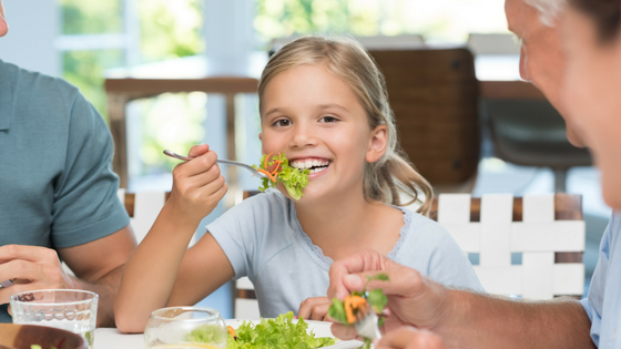 Young girl eating a salad at the table